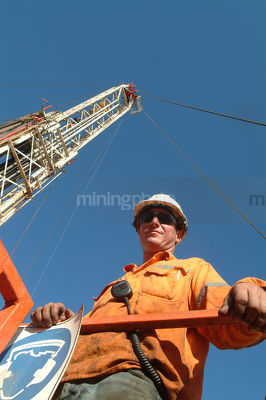 Oil and gas rig worker looking straight down into camera from a walkway with the derrick tower behind.  vertical shot. - Mining Photo Stock Library