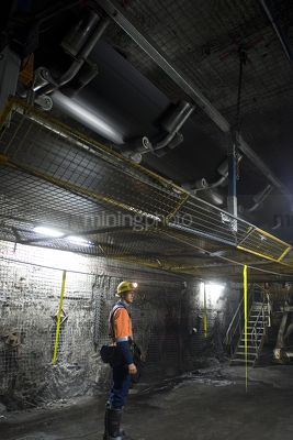 Underground coal mine worker standing still under moving coal conveyor - Mining Photo Stock Library