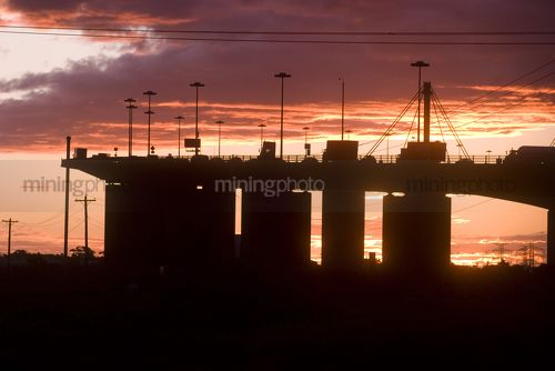 Sunset Silhouette image of traffic moving on large bridge.  great colour in sky. - Mining Photo Stock Library