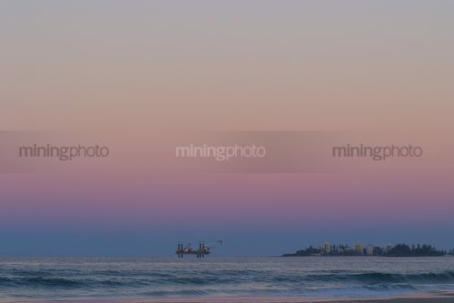 Offshore desalination plant drill rig working close to shore with headland and residents cloes by.  beach and waves in foreground. shot at sunset, good colours. - Mining Photo Stock Library
