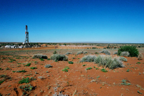 Oil and gas rig drilling in the harsh Australian desert.  image shows desert sand and shrubbery and flat ground to horiszon.  space for text.  generic image. - Mining Photo Stock Library