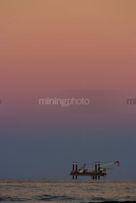 Offshore drill rig getting ready to drill. fabulous sky colours with lots of sky in the shot.  desalination plant. vertical image. - Mining Photo Stock Library