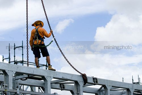 Construtcion worker in full safety harness clipped into crane rigging and standing on top of bridge beam. - Mining Photo Stock Library