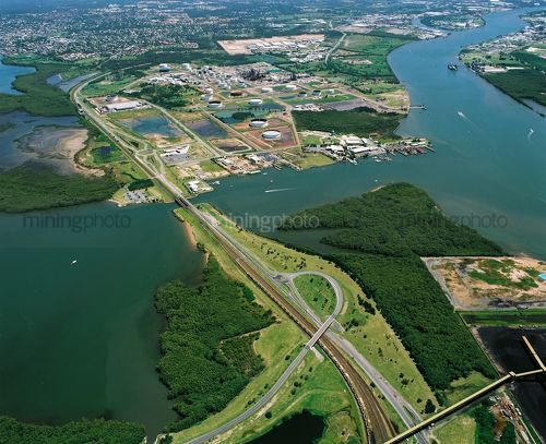 Aerial view of city freeway, water treatment plant and mangrove river. - Mining Photo Stock Library