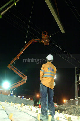 Infrastructure worker observing pre cast concrete crane lift during night works.  vertical image. - Mining Photo Stock Library