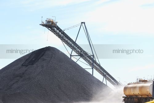 Water cart spraying water wioth coal stockpile and loader in background. - Mining Photo Stock Library