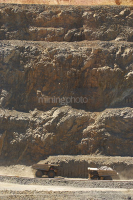 Loaded haul truck passes empty truck on gold mine haul road with high walls behind.  vertical shot - Mining Photo Stock Library