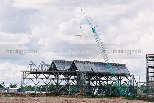 Cranes lifting roofing into place over steel construction for building of a factory  - Mining Photo Stock Library