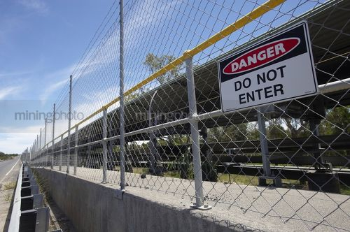 Covered coal conveyor behind wire fence with do not enter sign posted. - Mining Photo Stock Library