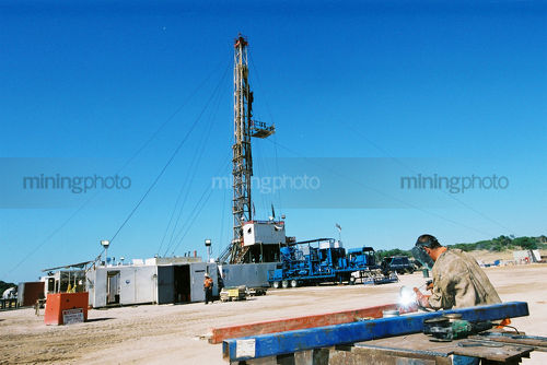 Welder on drill rig welding with sparks. drill derrick in background. - Mining Photo Stock Library