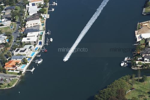 Aerial shot of jetski or small water craft on canal with residential houses all around. - Mining Photo Stock Library