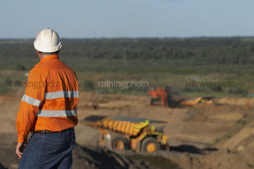 Mine worker in full PPE observing haul truck and mine workings at open cut mine. - Mining Photo Stock Library