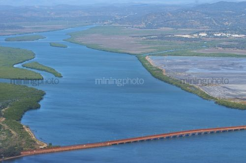 Overland conveyor spanning a river carrying bauxite from shipping to refinery.  aerial image with magroves and river system in background. - Mining Photo Stock Library