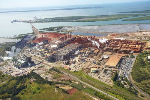 Wide aerial photo of a bauxite alumina refinery.  clearly depicts wharf shipping and all areas of processing plant. - Mining Photo Stock Library