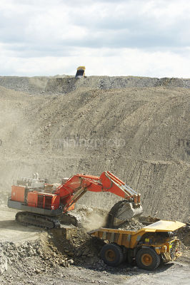 Vertical wide aerial photo of large excavator loading a 789 haul truck in open cut coal mine.  haul truck dumping overburden on stockpile in background. - Mining Photo Stock Library