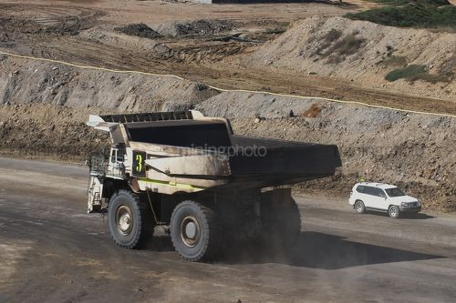 Haul truck and light vehicle pass on haul road in open cut mine site. - Mining Photo Stock Library