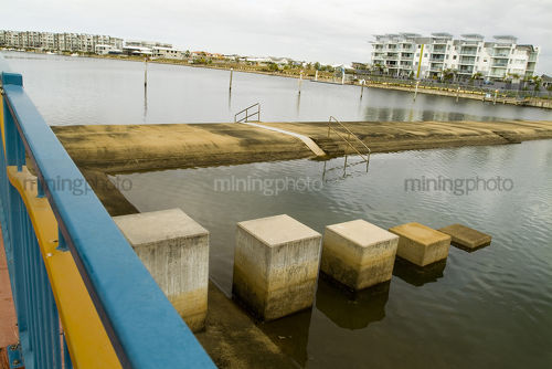 Water weir in tidal river amongst residential living - Mining Photo Stock Library