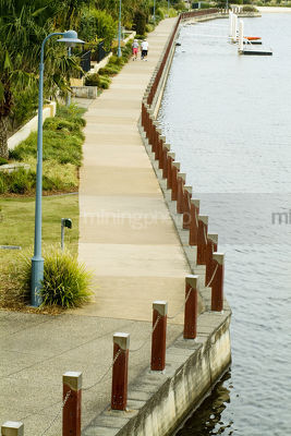 People walking along walk way next to lake with established landscaping beside - Mining Photo Stock Library