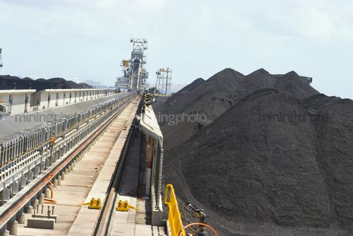 Coal spreader and reclaimer at terminal.  shot looking along tracks with coal stockpiles adjacent. - Mining Photo Stock Library
