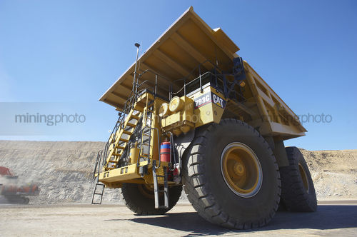 Dramatic photo of a haul truck in open cut coal mine.  shot from ground level almost under front wheel.  blue sky behind. - Mining Photo Stock Library