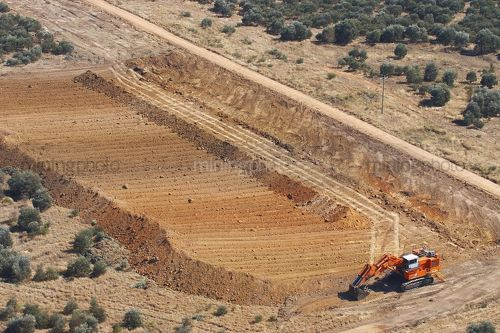 Excavator stripping topsoil prior to mining.  unsual photo taken as an aerial. - Mining Photo Stock Library