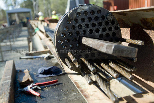 Steel wire cable foundation being assembled on outdoor site with workers in PPE out of focus in background. - Mining Photo Stock Library