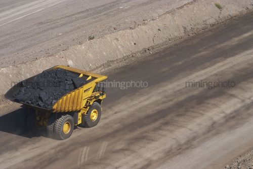 Loaded haul truck moving coal in open cut coal mine.  aerial shot. - Mining Photo Stock Library