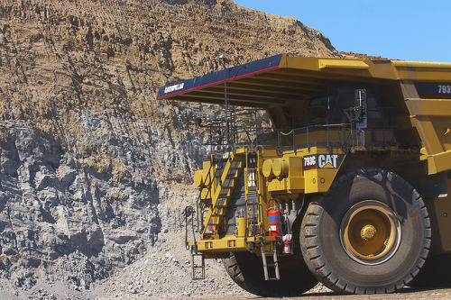 Close up photo of yellow haul truck in open cut coal mine with coal high walls behind. - Mining Photo Stock Library