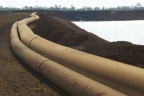 Water pipes to tailings holding dam on a mine site. - Mining Photo Stock Library