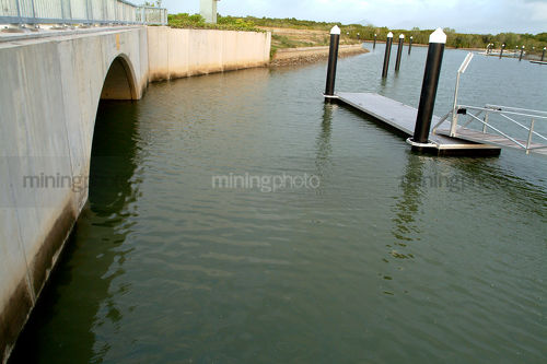 Road bridge into clean waterfront property subdivision. jettys and pontoons in water. - Mining Photo Stock Library