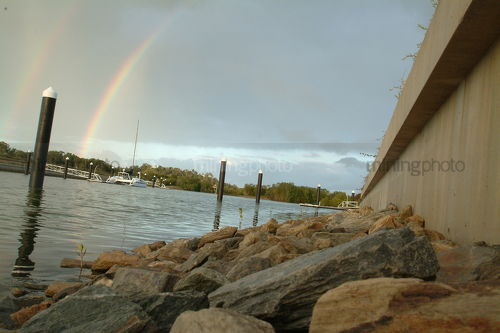 Rainbow over water in waterfront property subdivision - Mining Photo Stock Library