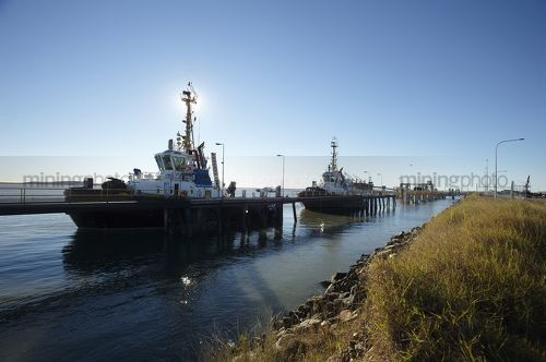 Tugboats berthed at wharf in early morning light.  blue sky behind. - Mining Photo Stock Library
