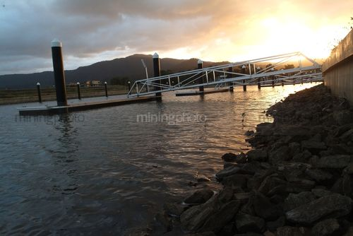 Sunset with jetty to a pontoon in foreground.  residential property. - Mining Photo Stock Library