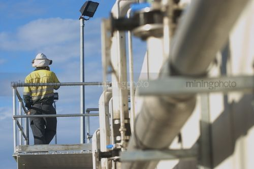 Mine site worker in full PPE using radio communications.  dramtaic shot of water treatment pipe in foreground.  worker shot from behind.