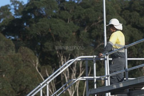 Worker in full PPE talking on radio while looking out over water treatment plant.  worker is at the top of walkway with one hand on railing. - Mining Photo Stock Library