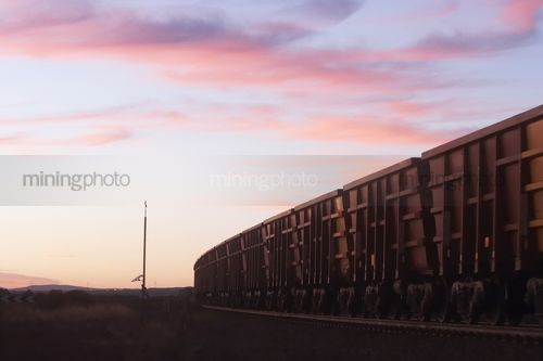 Iron ore train passing solar panel instrument tower in early morning light. - Mining Photo Stock Library