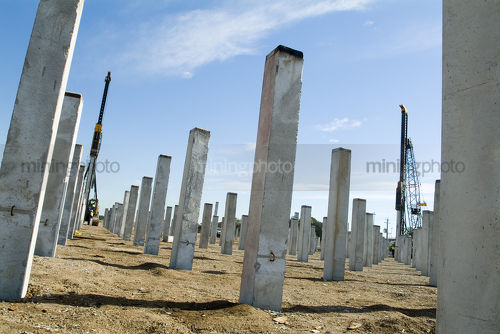 Piledriver hammers pre cast concrete piers into the ground as foundation - Mining Photo Stock Library