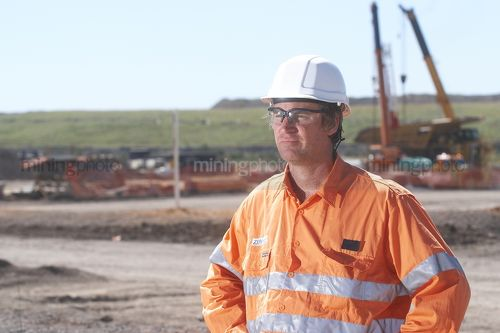Worker in full PPE looking across the camera near the workshop at a mine site. - Mining Photo Stock Library