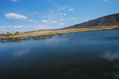 Mining machinery at open cut mine site.  photo shot from across a water storage dam. - Mining Photo Stock Library