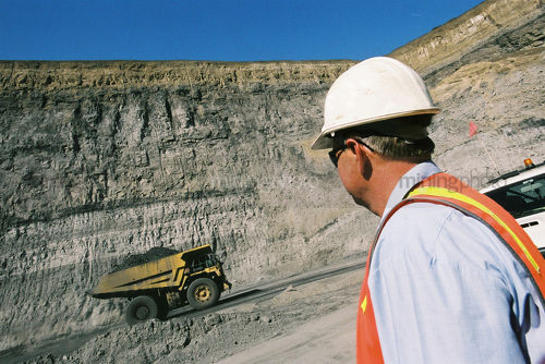 Mine site supervisor observing loaded haul truck with coal driving along ramp an access road in open cut coal mine. - Mining Photo Stock Library