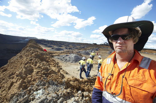 Mine site worker looking straight at the camera in open cut mine.  team workers pointing and working behind.  camera framed for double page spread. - Mining Photo Stock Library