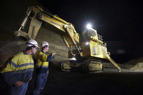 Shot at night, two 2 mine site workers in full PPE down in the open cut coal mine pit discussing next move with large excavator with lights on in the background. - Mining Photo Stock Library