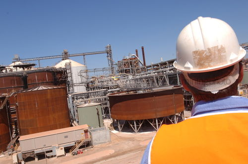 Worker in full PPE looking over refinery site.  shot from behind mine site worker. - Mining Photo Stock Library