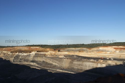Wide photo of open cut coal mine.  digger, haul trucks and machinery in operation.  high walls and coal seam. - Mining Photo Stock Library