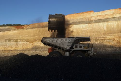 Generic photo of digger bucket loading coal into haul truck in open cut mine.  high walls and coal seam and blue sky in background. - Mining Photo Stock Library