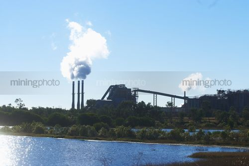 Water storage dam in foreground with generic refinery and industry in background. - Mining Photo Stock Library