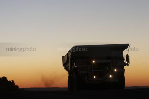 Silhouette photo of a haul truck coming over a hill in an open cut mine.  dusk and sunset behind. great generic shot. - Mining Photo Stock Library