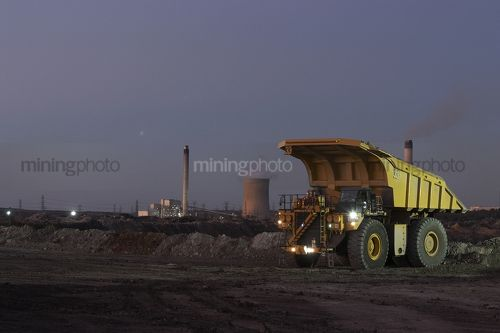 Dusk photo of haul truck unloading overburden in open cut coal mine.  power station in background. - Mining Photo Stock Library