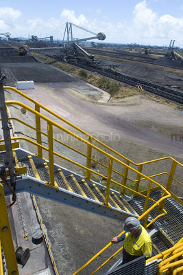 Mine site worker in full PPE walking down stairs with 3 three points of contact.  coal terminal with reclaimers in the background.  vertical photo. - Mining Photo Stock Library