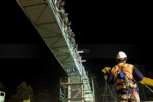 Rigger worker in full PPE including a harness working under a bridge at night.  crane and scaffolding in the background.  shot from behind. - Mining Photo Stock Library